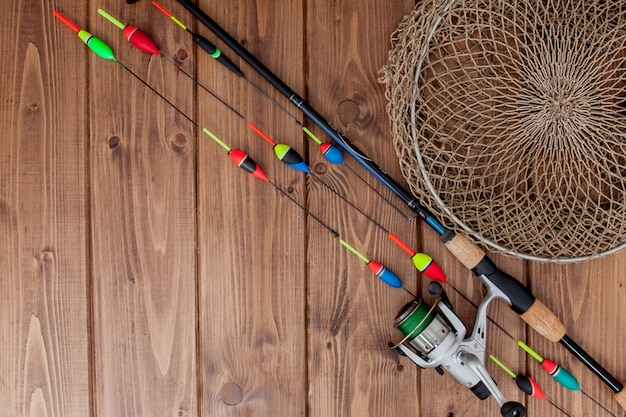 Fishing rod fishing float and lures on beautiful blue wooden