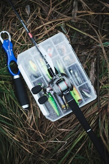 Fishing rod over the fishing lure transparent plastic box on grass