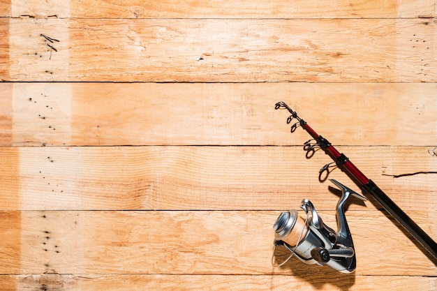 Fishing rod and fishing reel on wooden backdrop