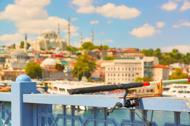 Fishing rod on galata bridge with istanbul panorama in the background. tourism in turkey.