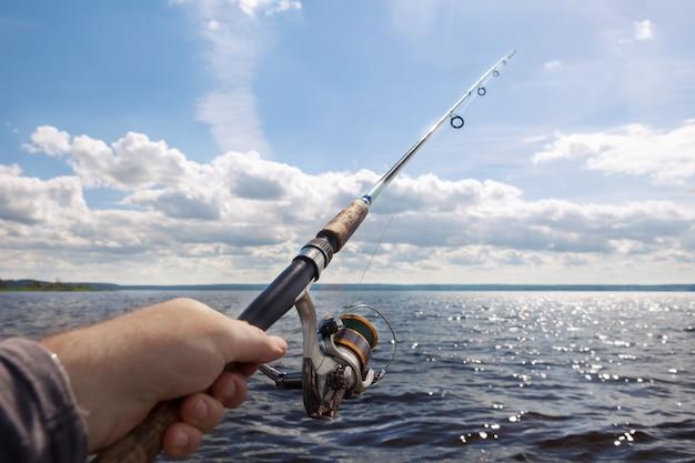晴れた日に川で手に釣り竿。