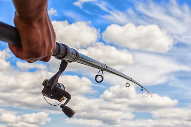 男の手で青空の背景に釣り竿