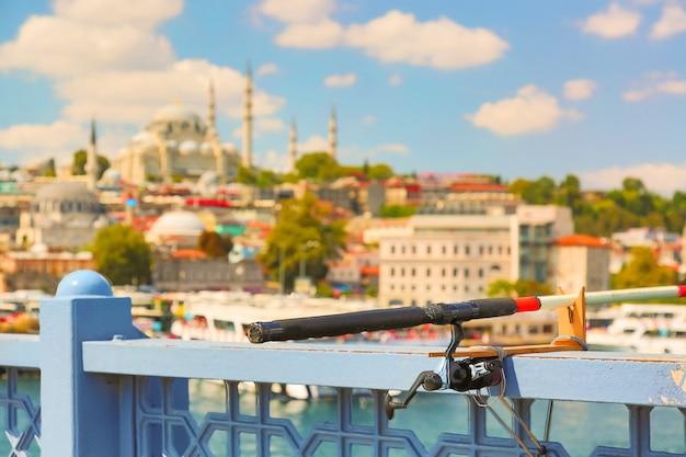 Рыболовная удочка на мосте галата с панорамой стамбула на заднем плане. туризм в турции.