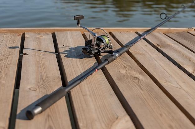 Удочка или рыболов, лежащий на лесном берегу над рекой или озером летом крупным планом