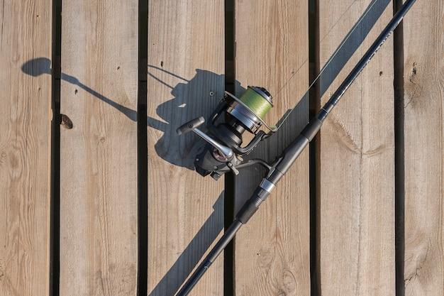 Удочка или рыболов, лежа на деревянной поверхности, вид сверху