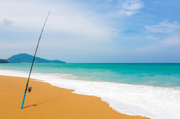 Fishing rod in sand of tropical beach