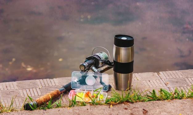 Удочка, спиннинговая катушка и чашка горячего кофе на берегу речного пирса