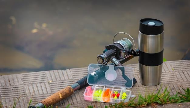 Удочка, спиннинговая катушка и чашка горячего кофе на берегу речного пирса Premium Фотографии