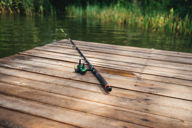 Удочка, спиннинговая катушка на пирсе, берег реки. туманное утро. дикая природа. концепция сельского отдыха. статья о рыбалке.