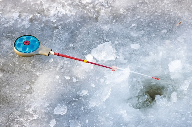 Fishing rod for winter fishing lies on ice