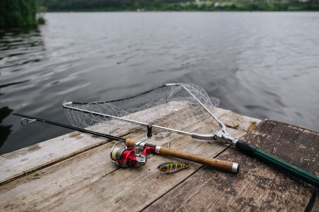 Fishing rod with lure and net on wooden pier over idyllic lake