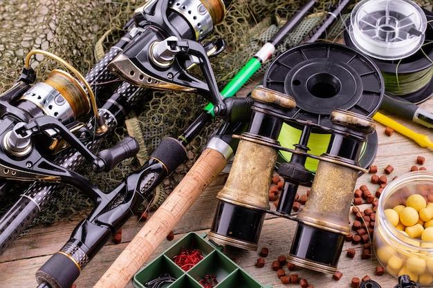 Удочки и спиннинги в составе с аксессуарами для рыбалки на старой поверхности на столе