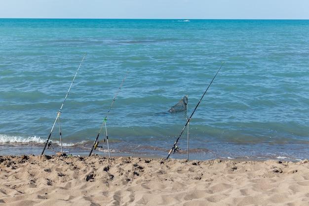 Удочки стоят на песчаном пляже. фиксированная удочка, устанавливаемая на пляже возле прибоя во время прилива. голубое небо с облаками, бирюзовое море.