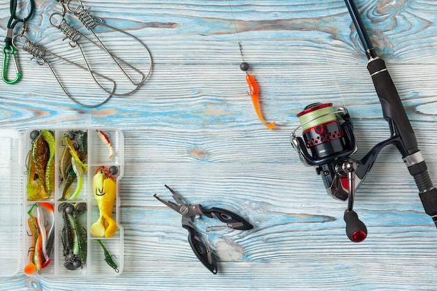 Fishing spinning, hooks and lures on blue wooden background.top view