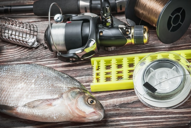 Fishing tackle and fished bream on a wooden table