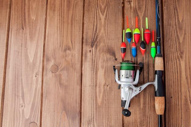 釣り道具-美しい青い木製の背景、コピースペースに釣り竿の浮きとルアー。