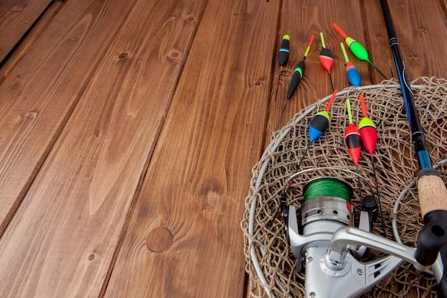釣り道具-美しい青い木製のスペース、コピースペースの釣り竿釣りフロートとルアー