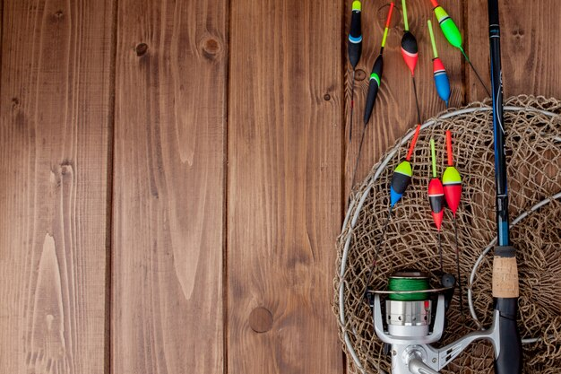 Fishing tackle - fishing rod fishing float and lures on beautiful blue wooden background, copy space