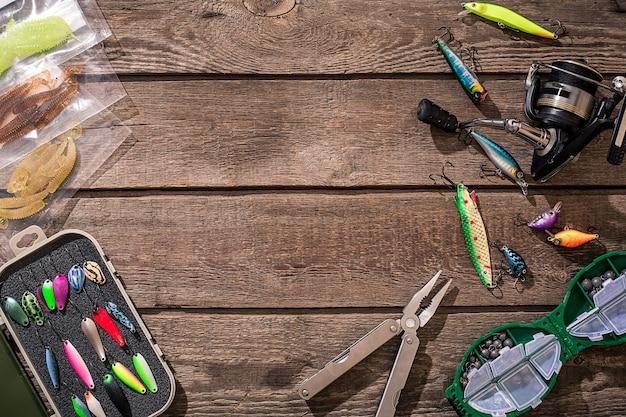 낚시 도구 - 낚시 회전, 낚싯줄, 후크 및 미끼가 나무 배경에 있습니다. 평면도. 공간을 복사합니다. 정물