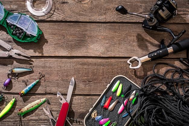 낚시 도구 낚시 회전 낚싯줄 후크와 나무 배경에 미끼