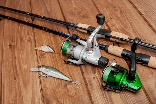 釣り道具-コピースペースのある木製の背景にスピニング、フック、ルアーを釣ります。