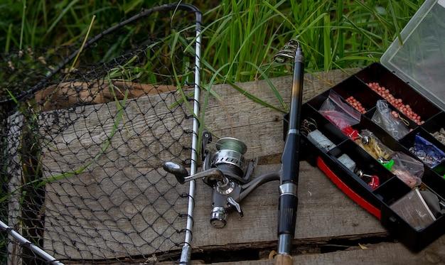 강둑에 낚시 도구, 미끼 막대, 물레, 물고기. 자연. 선택적 초점
