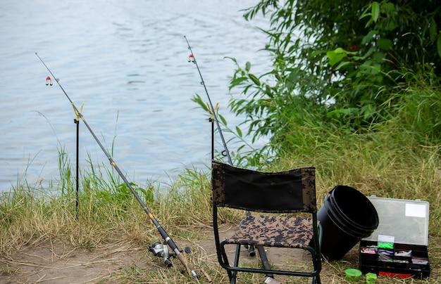 강둑에 낚시 도구, 미끼 막대, 물레, 물고기. 선택적 초점