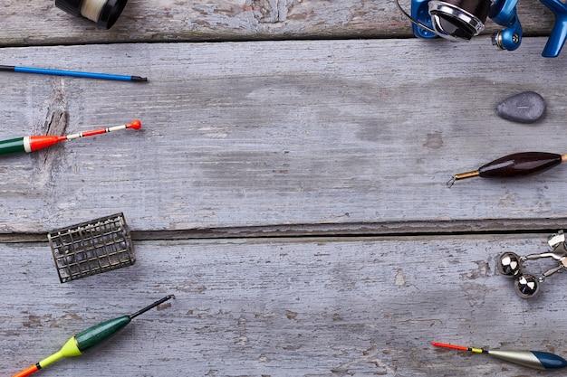 Рыболовные снасти на деревянных фоне. оборудование для ловли рыбы. рыбалка как хобби.