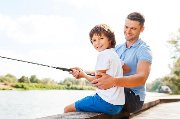 Совместная рыбалка - это весело. веселый отец и сын вместе ловят рыбу, пока маленький мальчик смотрит в камеру и улыбается