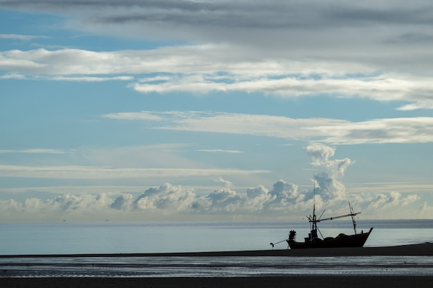 Fishing vessel with beautiful cloud sky on the beach in the morning