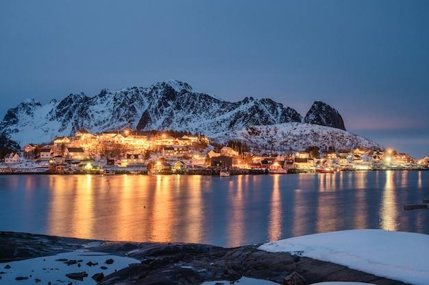 Lofoten 섬에서 겨울에 해안선에 산맥으로 어촌 조명