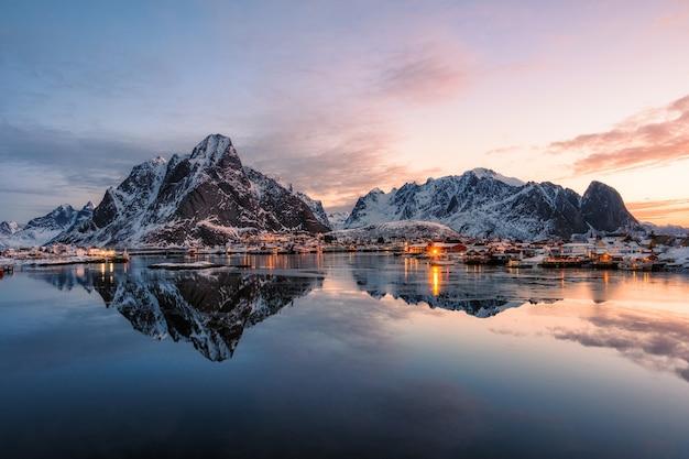 Рыбацкая деревня со снежной горой на рассвете в рейне, лофотенские острова, норвегия