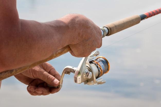 강에서 스피닝으로 낚시하는 남자는 손과 스피닝 릴 가까이에서 물고기를 잡는다