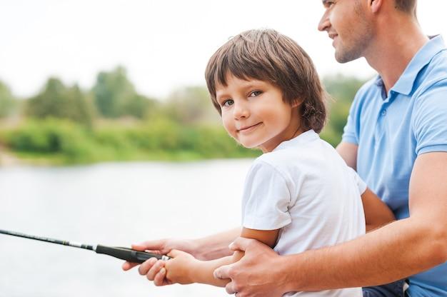 Рыбалка с отцом. веселый отец и сын вместе ловят рыбу, пока маленький мальчик смотрит в камеру и улыбается