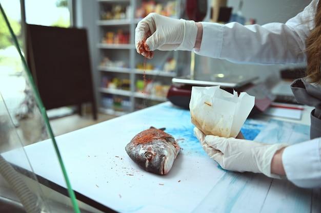 Fishmonger는 해산물 가게의 카운터에 누워 있는 쿨데스 도라도 물고기에 장갑을 낀 손으로 조미료를 뿌리고 있습니다. 식품 소비주의, 요리, 해산물 소매