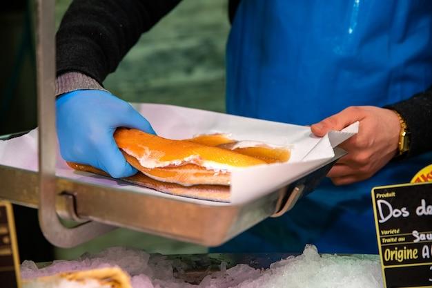 Торговец рыбой взвешивает рыбу на весах