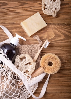 Fishnet shopping bag with ethical eco-friendly cleaning household products: sisal brush, natural luffa, bamboo toothbrush, organic soap in bottle, wooden pins. conscious consumption concept