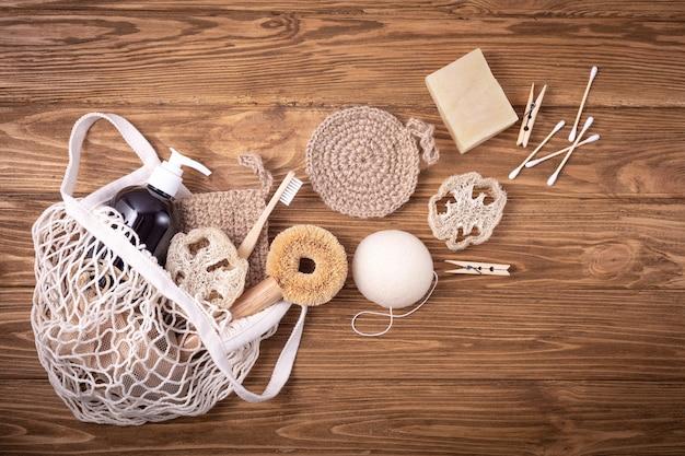 Ажурная сумка для покупок с этическими экологически чистыми чистящими средствами для дома: щетка из сизаля, натуральная люфа, бамбуковая зубная щетка, органическое мыло в бутылке, деревянные булавки, бутоны, многоразовые накладки для лица, губка конжак.