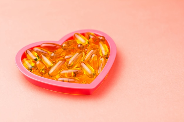 Fishoil capsules in the heart shape frame on pink with copy space.