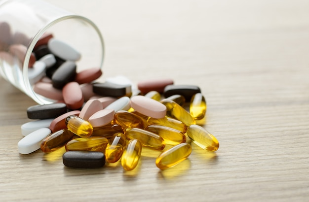 Fishoil capsules and multivitamin supplements out of the small glass on the wooden table with copy space.