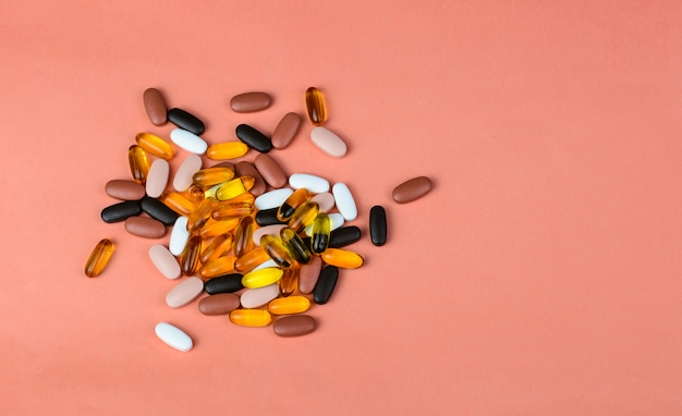 Fishoil capsules and multivitamin supplements on pink