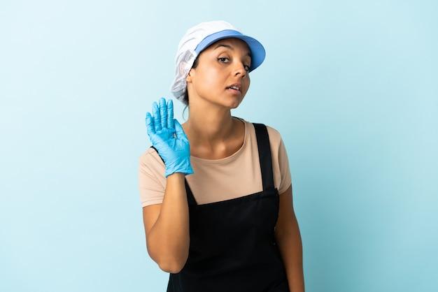耳に手を置いて何かを聞いているフィッシュワイフアジアの女性