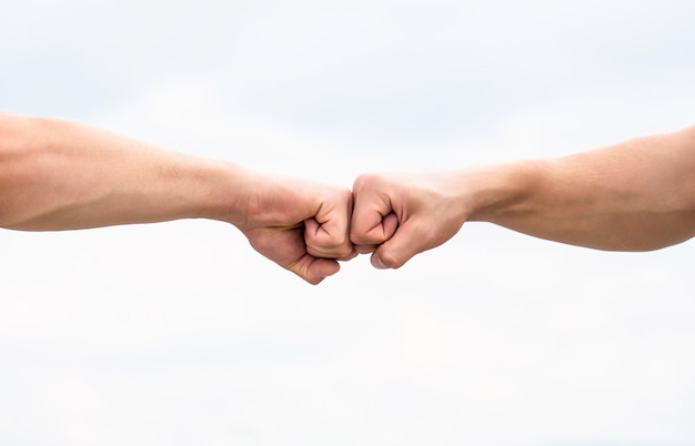 주먹 범프. 두 주먹의 충돌. 대결, 경쟁의 개념입니다. 존경 또는 승인을 주는 제스처. 팀워크와 우정. 파트너십 개념입니다. 주먹 범프를 주는 남자. 부딪치는 주먹