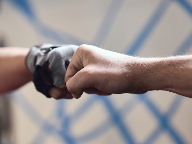 Fist bump detail, one with gym glove, on unfocused background