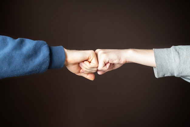 Fist bump or knuckle bump between two friends f