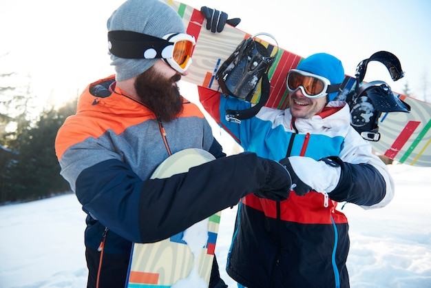 Fist bump of two male snowboarders