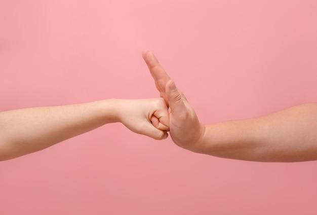 Fist hands of woman and man on pink background, man stop woman standoff