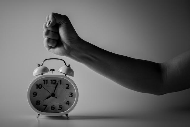 目覚まし時計を破壊するために拳が破壊されています。戦いと時間制限の概念。