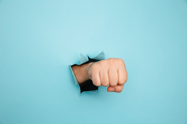 Fist punching through blue paper wall. threat, fight and combat sports. push through the wall