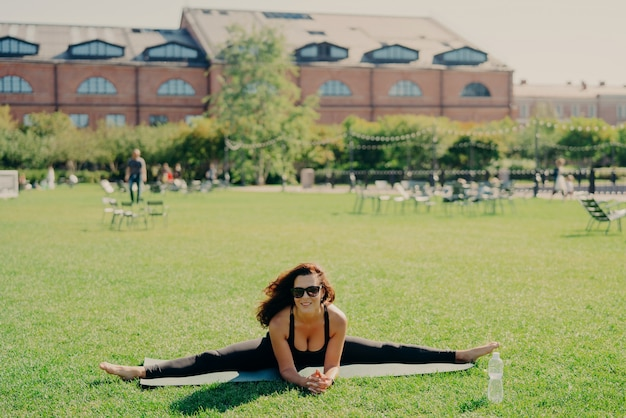 Fit active european woman does pilates on fitness mat wears sunglasses and sportswear shows great progress poses on green lawn has happy expression trains outside. fitness and stretching concept